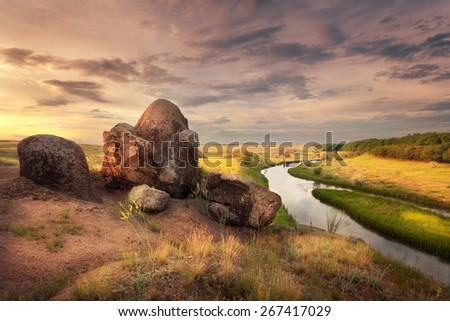 Beautiful summer sunset at the river with orange sky, clouds, rocks, yellow grass, flowers and water with reflection. Ukraine - stock photo