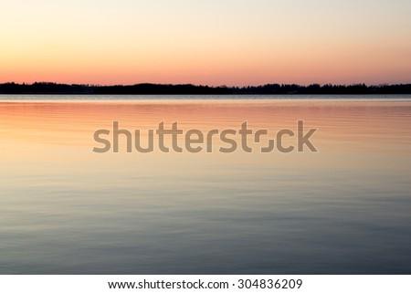 Beautiful summer sunset over a calm lake - stock photo