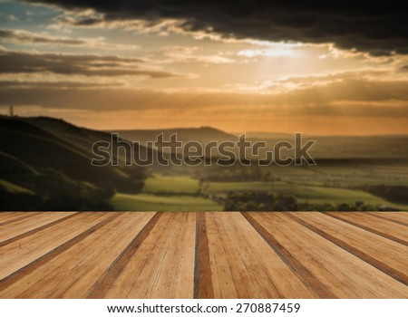 Beautiful Summer sunset over escarpment landscape with wooden planks floor - stock photo