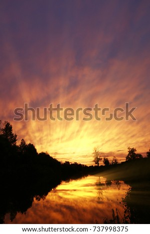 Beautiful summer sunset with red clouds and rays