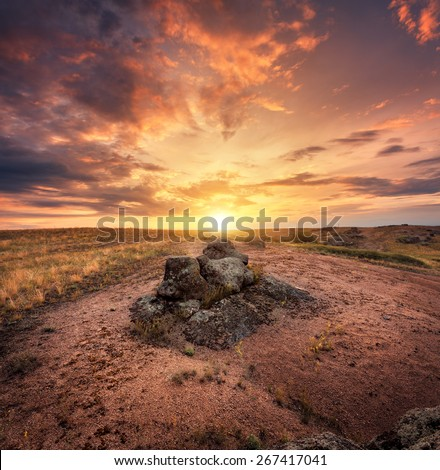 Beautiful summer sunset with red sky, orange clouds, rocks and yellow grass in Ukraine - stock photo
