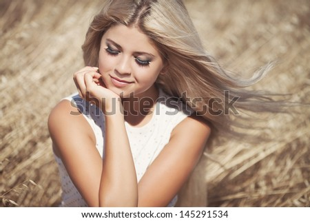 Beautiful summer woman smiling outdoors healthy girl at vacation in wheat field. Attractive happy blonde woman resting. Summer makeup hairstyle. long hair perfect skin. young woman outdoors. Elegant