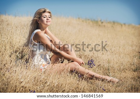 Beautiful summer woman smiling outdoors healthy girl at vacation in wheat field. Attractive happy blonde woman resting. Summer makeup hairstyle. long hair perfect skin. young woman outdoors - stock photo