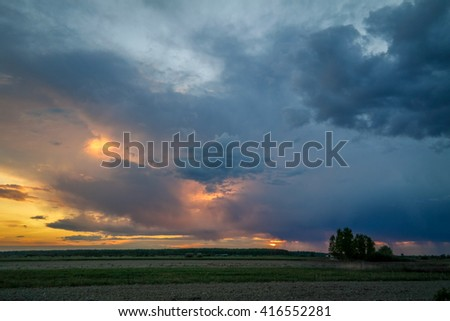 Beautiful sun rays through the stormy clouds to the forest and field. Amazing sunset while raining, in Romania. Heavy Rain at sunset