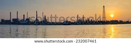 beautiful sun rising scene with oil ,gas refinery industry estate and marine tanker logistic port - stock photo