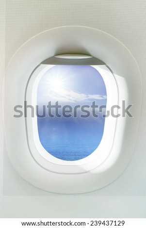beautiful sun shining over clear blue ocean through  frame of windows plane  use as background,backdrop - stock photo