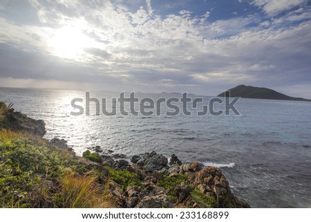Beautiful Sunny Day Over The Caribbean Sea With Islands, Clouds, Blue Skies, Clear Blue Water, And Rocky Shores. - stock photo
