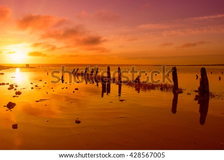 Beautiful sunny red sunset on the lake with stones, wooden posts and reflection, natural seasonal summer vacation background