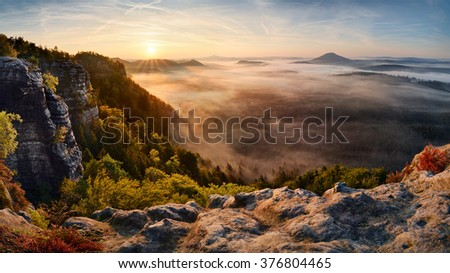 Beautiful sunrise above the forest valley of autumn National Park Bohemian Switzerland - stock photo