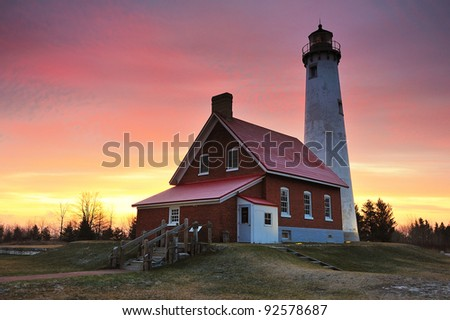Beautiful sunrise at Tawas Point Lighthouse, East Tawas, Michigan. USA Just a dusting of snow on the ground in this Michigan Winter scene. - stock photo