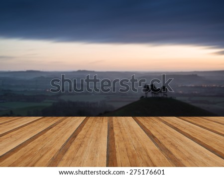 Beautiful sunrise dawn landscape of countryside overlooking brightly lit town in valley below with wooden planks floor - stock photo