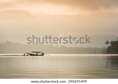 Beautiful sunrise in the morning, boat in the fog and nature background, Ratchaprapha Dam at Khao Sok National Park, Suratthani, Thailand. - stock photo