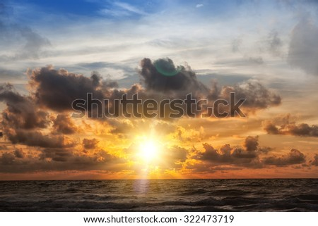 Beautiful sunrise in the sea with clouds - stock photo