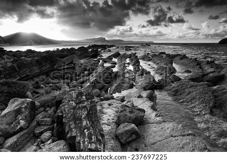 Beautiful sunrise landscape over Mupe Bay on Jurassic Coast in Dorset, England  black and white - stock photo