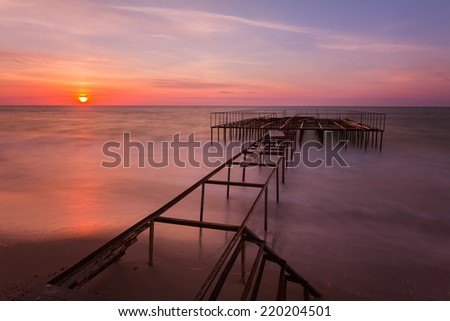 Beautiful sunrise landscape with a pier on background. Long exposure. - stock photo