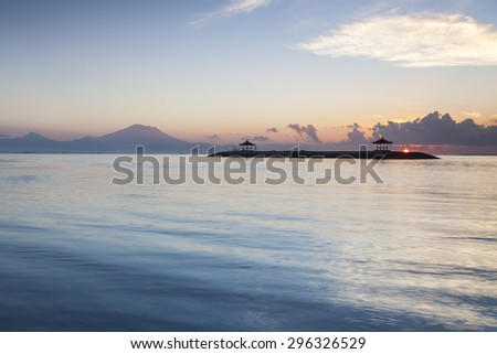 beautiful sunrise of the Sanur Beach at Bali, Indonesia. Slow motion of the wave create beautiful ripple with reflection of the sunlight.  - stock photo