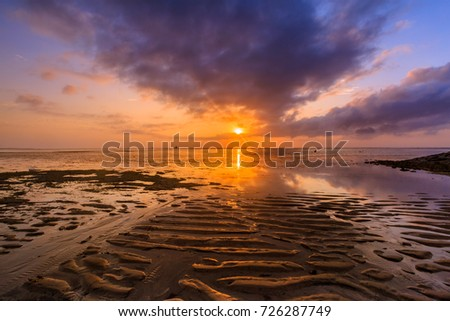 Beautiful sunrise on a beach in Bali Indonesia with colorful sky as background
