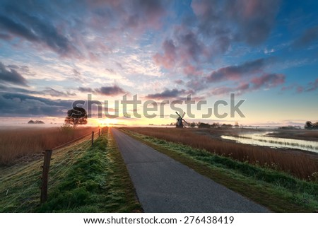 beautiful sunrise on dutch farmland with windmill and bicycle path - stock photo