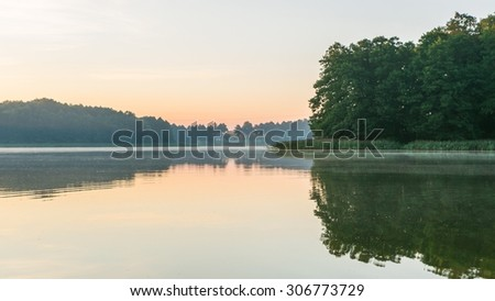 Beautiful sunrise over lake. Summertime tranquil landscape. - stock photo