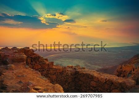 Beautiful sunrise over Masada fortress. Ruins of King Herod's palace in Judaean Desert. - stock photo