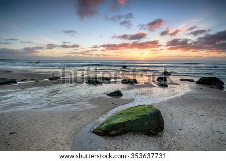 Beautiful sunrise over Pentewan Sands a large sandy beach near Mevagissey on the south coast of Cornwall - stock photo
