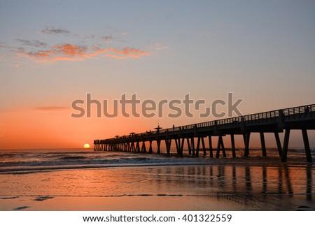 Beautiful sunrise over the ocean and pier, sun rising over horizon, beach illuminated with sunlight, Jacksonville Florida, USA. - stock photo
