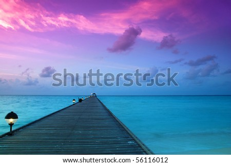 Beautiful sunrise over the sea and jetty in the Maldives, Indian Ocean - stock photo