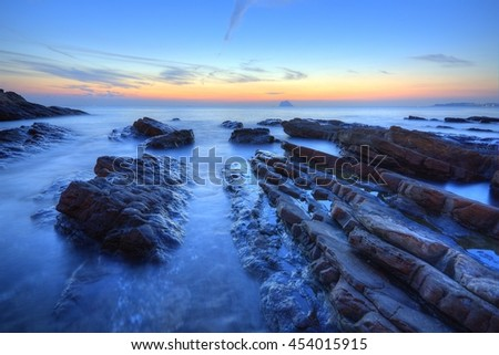 Beautiful sunrise scenery of a rocky beach on northern coast of Taiwan with an island on distant horizon & peculiar rock formations on seashore under dramatic dawning sky (Long Exposure Effect) - stock photo