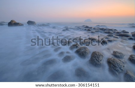 Beautiful sunrise scenery of the rocky coast in northern Taiwan with peculiar rock formations by the beach and an island at the distant horizon under dramatic dawning sky (long exposure effect) - stock photo