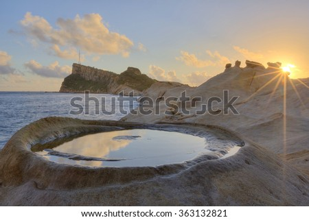 Beautiful sunrise sky reflecting on mirror-like rock formation at rocky beach of Yehliu Coast in northern Taiwan ~ Dramatic scenery of peculiar coastline in northern Taiwan - stock photo