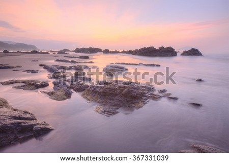 Beautiful sunrise sky reflecting on the rocky beach at Yilan Coast Geologic Park  ~ Spectacular scenery of intriguing rocky coastline in eastern Taiwan (Long Exposure Effect) - stock photo