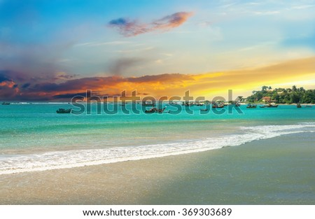 Beautiful sunrise, tropical beach white sand, turquoise ocean water . Boats of fishermen on the water. Palm trees and tropical vegetation on the coast. - stock photo