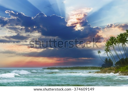 Beautiful sunrise, tropical beach white sand, turquoise ocean water . Palm trees and tropical vegetation on the coast. - stock photo