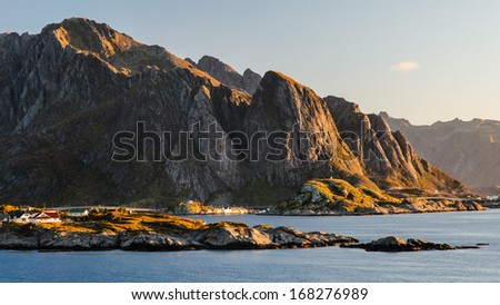 Beautiful sunrise view towards village of Reine and rugged mountains of Lofoten islands, Norway