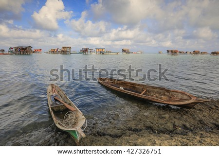 Beautiful sunrise with blue sky over a traditional boat at Pulau Maiga, one of famous tourist attraction at Semporna, Sabah, Malaysia.