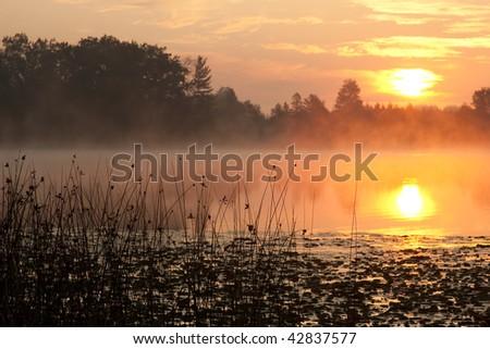 Beautiful Sunrise with Reflection on Lake - stock photo