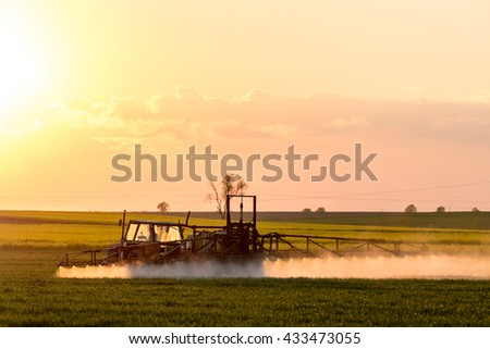 Beautiful sunset above spraying machine working on the green field - stock photo