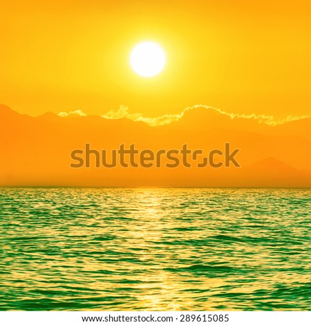 Beautiful sunset above the green sea with big shining sun and orange sky - stock photo