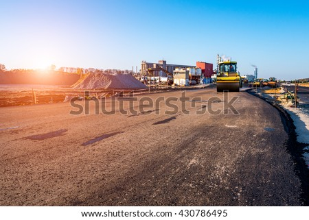 Beautiful sunset above the road rollers working on the new road construction site - stock photo
