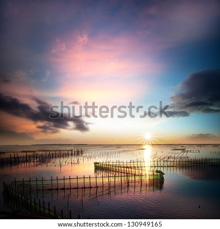beautiful sunset and cloud reflection on the sea and lake - stock photo
