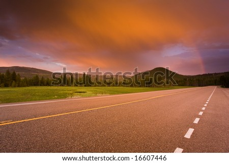 Beautiful sunset and rainbow over a road leading into distant mountains. - stock photo