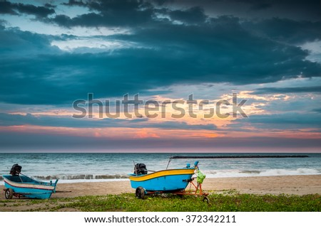 Beautiful sunset and sandy beach with fishing boat. Bright and dynamic sea beach sunset with bright blue skies and colorful clouds, Thailand - stock photo