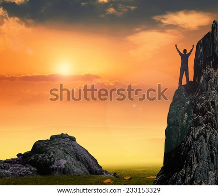 Beautiful sunset and silhouette of man with hands raised. - stock photo