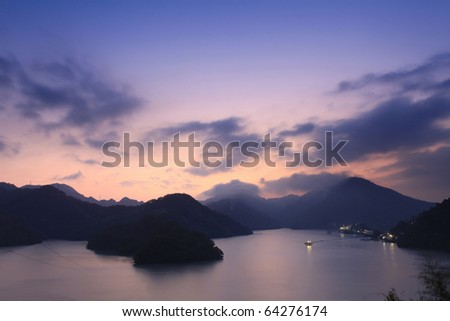 Beautiful sunset and silhouette of mountains in the reservoir - stock photo