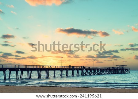 Beautiful sunset at Grange Jetty Adelaide Australia with people silhouettes  - stock photo