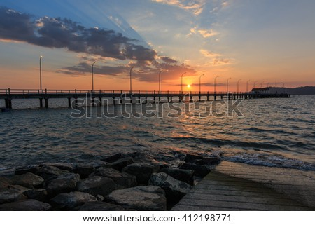 Beautiful sunset at Odec University Malaysia Sabah Jetty (silhouettes) , Bridge on beach in sunset and sea wave in asia ocean. - stock photo
