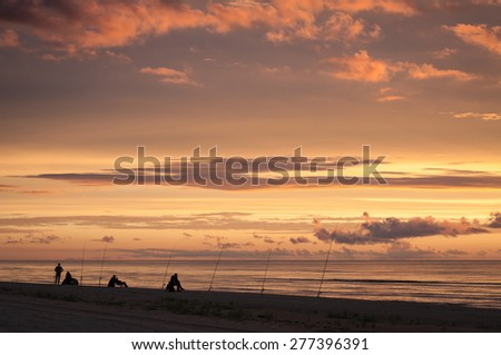 Beautiful sunset at the beach with several fishermen on the shore - stock photo