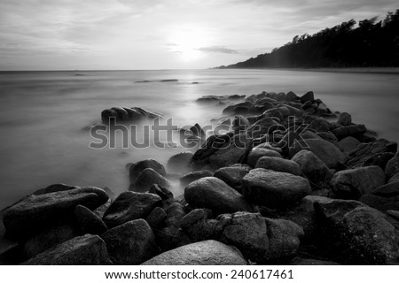 Beautiful sunset at the stone beach in black and white