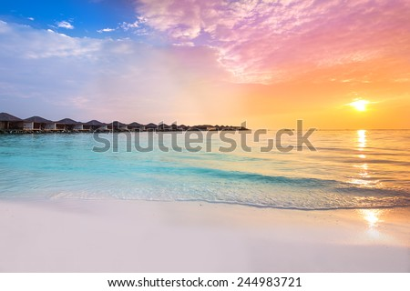 Beautiful sunset at tropical resort with overwater bungalows - stock photo