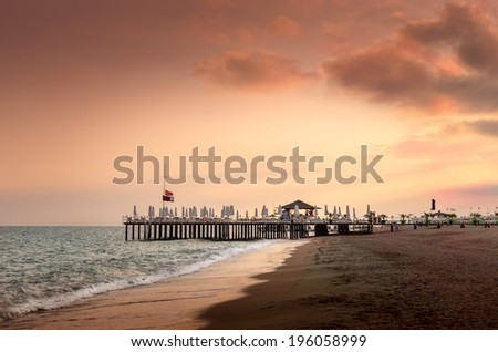 Beautiful sunset, beach with pier and sunbeds - stock photo
